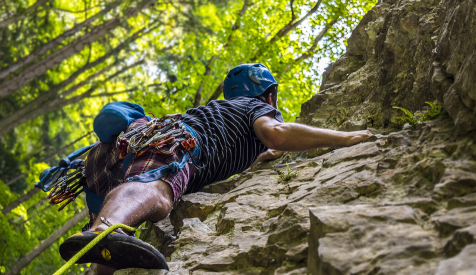 man climbing a craggy wall